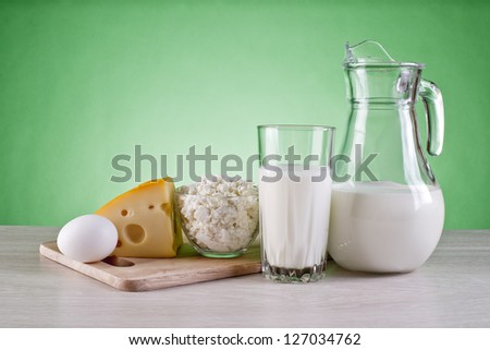 still life of dairy products and cutting boards on a green background #127034762