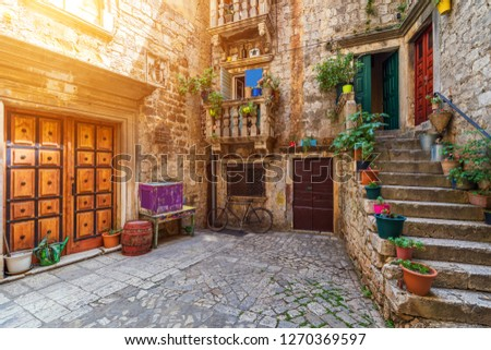 Narrow street in historic town Trogir, Croatia. Travel destination. Narrow old street in Trogir city, Croatia. The alleys of the old town of Trogir are very picturesque and full of charm. Croatia. #1270369597