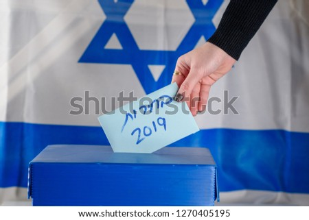 Election in Israel - voting at the ballot box. The hand of woman putting her vote in the ballot box. Israeli Flag on background. Hebrew text Elections 2019. #1270405195