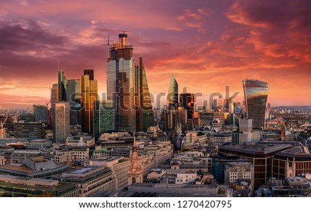 Fiery sunset over the urban skyline of the financial district City of London, United Kingdom
