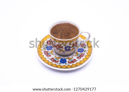Turkish coffee in a white cup isolated on a motifed background (path included). Traditional Turkish Coffee