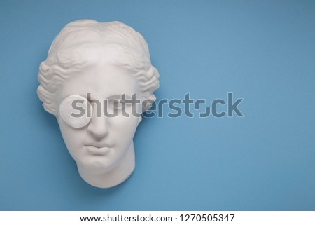 Face cleaning, removing makeup. Aphrodite face on blue background #1270505347