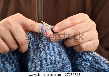 Hands of a young woman knitting with blue wool #127050815