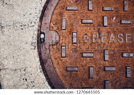 Rusty metal grease trap cover on concrete floor.  Royalty-Free Stock Photo #1270665505