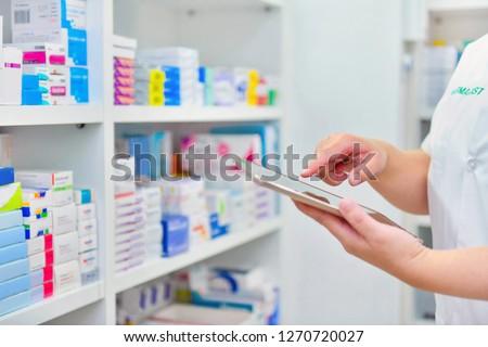 Pharmacist holding computer tablet Using for filling prescription in pharmacy drugstore.  #1270720027