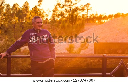 Nerva, Spain- November 30, 2018: Handsome senior man posing standing leaning on handrail with sun flare at sunset #1270747807