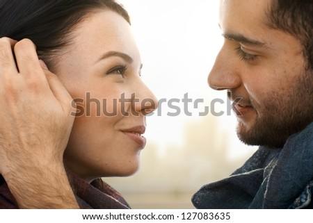 Closeup photo of romantic kissing couple, side view. #127083635