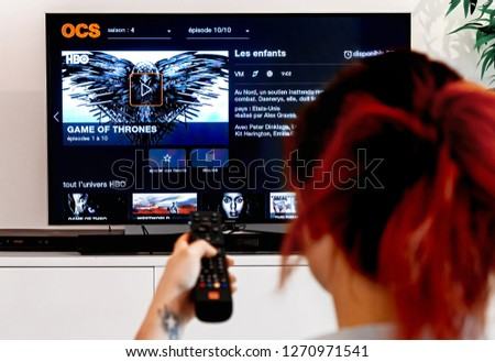 Benon, France - December 30, 2018: Woman Holding a TV remote and watch Game of thrones, an original creation of HBO industry. Created by David Benioff and D. B. Weiss, broadcast since 2011 on HBO #1270971541