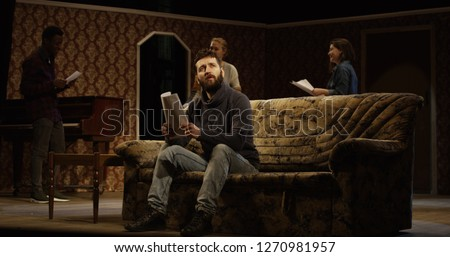 Medium shot of an actor reciting his lines on a sofa while other actors rehearsing in the background Royalty-Free Stock Photo #1270981957