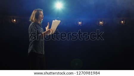 Medium close-up of an actress rehearsing a monologue in a theater while holding her script #1270981984