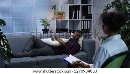 Medium shot of young man lying on a couch while talking to a psychologist #1270984033
