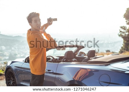 Smiling boy with yellow sweatshirt and black pants recording himself with camera in viewpoint with blue luxury sports car #1271046247