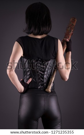 Stock photo of a sexy female assassin with a bat, wearing black leather. #1271235355