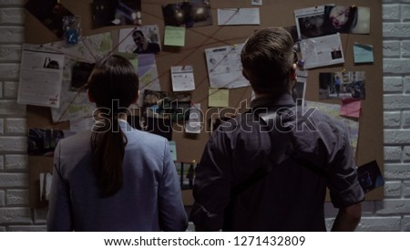 Secret agency teammates searching for criminal movements on investigation board Royalty-Free Stock Photo #1271432809