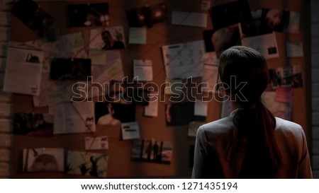 Lady private agent looking at crime investigation board, chasing serial killer Royalty-Free Stock Photo #1271435194