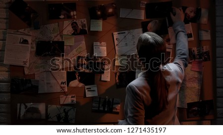 Smart detective looking attentively at investigation board, evaluating clues Royalty-Free Stock Photo #1271435197