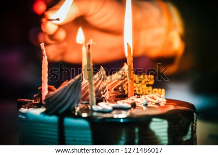 Close view of lighting candles with matchstick on a chocolate cake. #1271486017