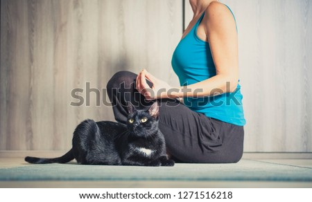 woman doing yoga at home - black cat sitting next to her