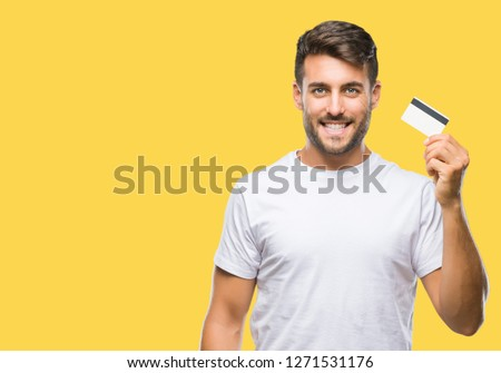 Young handsome man holding credit card over isolated background with a happy face standing and smiling with a confident smile showing teeth