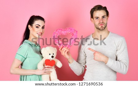 Handsome man and pretty girl in love. Romantic couple in love. Cute gift concept. Valentines day and love. Man and woman couple in love hold heart valentines cards and teddy bear on pink background. #1271690536