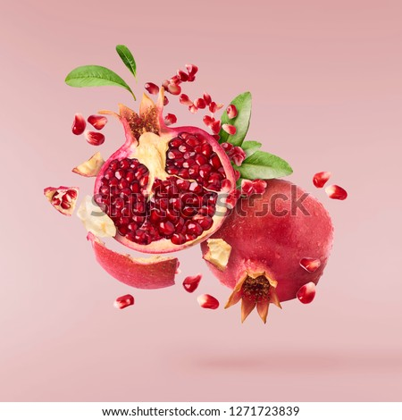 Flying in air fresh ripe whole and cut pomegranate with seeds and leaves isolated on pastel pink background. High resolution image #1271723839