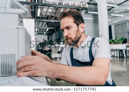 close up view of male handyman repairing copy machine in modern office  #1271757745