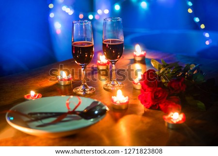 Valentines dinner romantic love concept / Romantic table setting decorated with fork spoon on plate and couple champagne glass roses with candlelight on wooden table dinner night light background  #1271823808