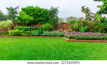 Beautiful English cottage garden, colorful flowering plant on smooth green grass lawn and group of evergreen trees in good care maintenance landscaping of a public park under white sky  #1271859091