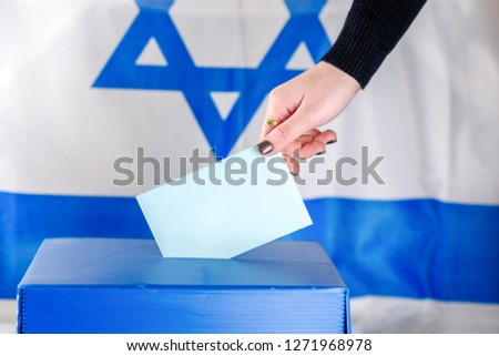 Israeli Young woman putting a ballot in a ballot box on election day. Close up of hand with white votes paper on Israel flag background. Mocup, space for text. #1271968978