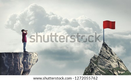 Man on a mountain peak looking through binoculars to a red flag. The concept of reaching goals. Royalty-Free Stock Photo #1272055762