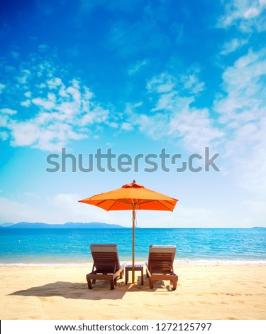 Two lounge chairs with sun umbrella on a beach #1272125797
