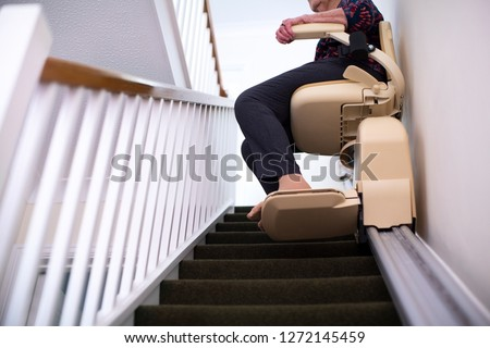 Detail Of Senior Woman Sitting On Stair Lift At Home To Help Mobility Royalty-Free Stock Photo #1272145459