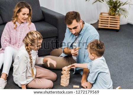 two parents playing blocks wood tower game with children on floor in apartment #1272179569