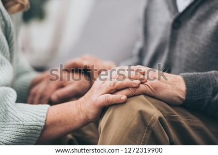 cropped view of retired couple holding hands  #1272319900