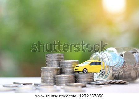Miniature yellow car model on stack of coins money in glass bottle on nature green background, Saving money for car, Finance and car loan, Investment and business concept. #1272357850