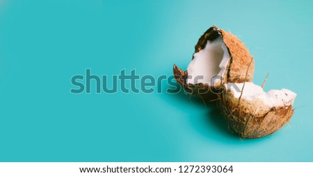 Coconut on a blue background with space for text. Half of coconut on turquoise background. Tropical fruit concept #1272393064