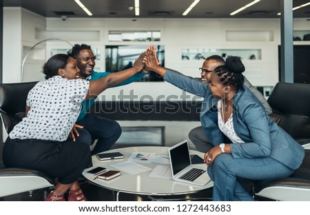 Friendly successful all african business team give high five together in office, excited happy employees celebrating corporate victory, african workers teambuilding concept Royalty-Free Stock Photo #1272443683