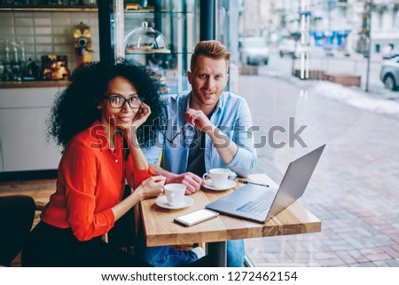Portrait of two prosperous multicultural owners of common cafeteria smiling at camera while sitting at modern laptop computer and collaborating on development of own successful business startup #1272462154