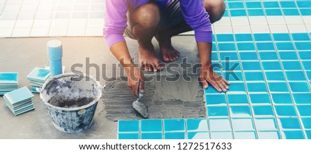 Professional Industrial construction men worker tiling Floor and Wall ceramic Swimming pool tiles floor.Skilled workers Aptitude for architecture concept.  #1272517633