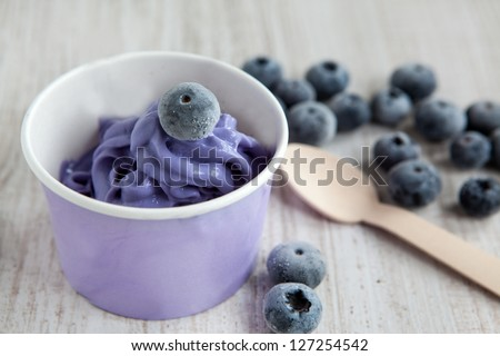 Serving of frozen creamy ice yoghurt  with whole fresh blueberries and wooden spoon Royalty-Free Stock Photo #127254542