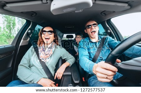 Cheerful young traditional family has a long auto journey and singing aloud the favorite song together. Safety riding car concept wide angle inside car view image.  #1272577537