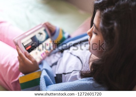 Girl Using Digital Tablet While Lying In Bed #1272601720