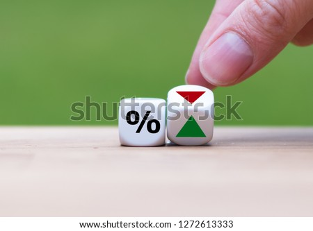 Hand is turning a dice and changes the direction of an arrow symbolizing that the interest rates are going down (or vice versa) #1272613333