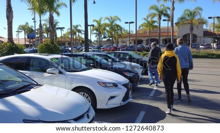 A man and his teen daughters shopping for used cars                               Royalty-Free Stock Photo #1272640873
