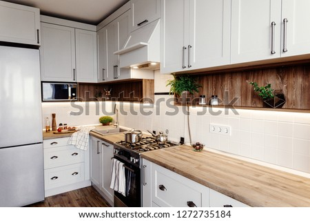 Stylish kitchen interior design. Luxury modern kitchen furniture in grey color and steel oven,fridge, sink, wooden tabletop, pots,. Gray cabinets in scandinavian style. Home renovation. #1272735184