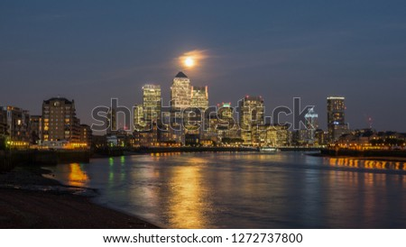 View of Canary Wharf buildings at night under a full moon with light reflections on the water in London, England, United Kingdom #1272737800