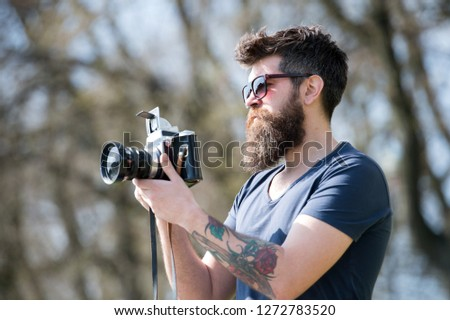 Man bearded hipster photographer hold vintage camera. Photographer with beard and mustache amateur photographer nature background. Man with long beard busy with shooting photos. Photographer concept. #1272783520