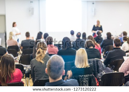 Business and entrepreneurship symposium. Female speaker giving a talk at business meeting. Audience in conference hall. Rear view of unrecognized participant in audience. Copy space on whitescreen. #1273120222