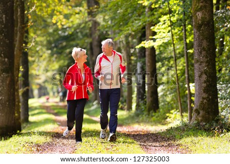 Senior Couple doing sport outdoors, jogging on a forest road in the autumn #127325003