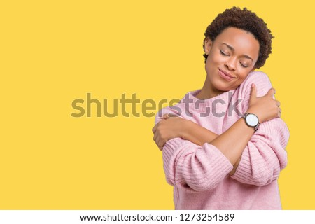 Beautiful young african american woman over isolated background Hugging oneself happy and positive, smiling confident. Self love and self care #1273254589